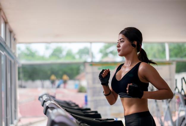 Sprawności fizycznej młoda kobieta ćwiczy z słuchającą muzyką i bieg na bieżni maszynie w gym