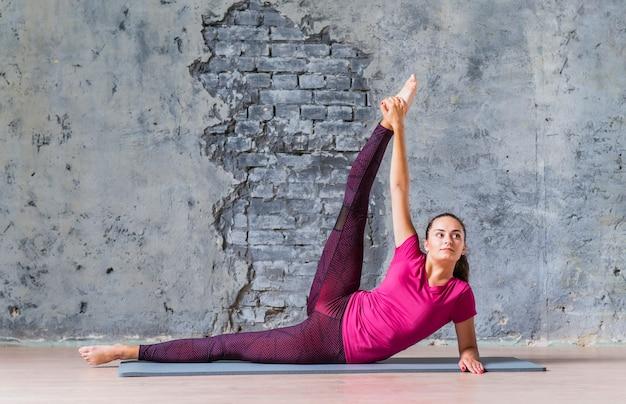 Sprawności fizycznej młoda kobieta robi ćwiczeniom przeciw popielatej ścianie