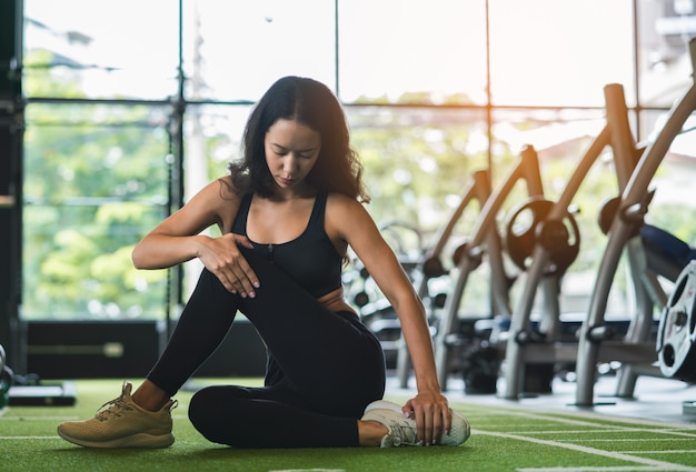 Sprawności fizycznej młoda kobieta rozciąga jej nogę ogrzewać na podłoga przy gym sporta klubem