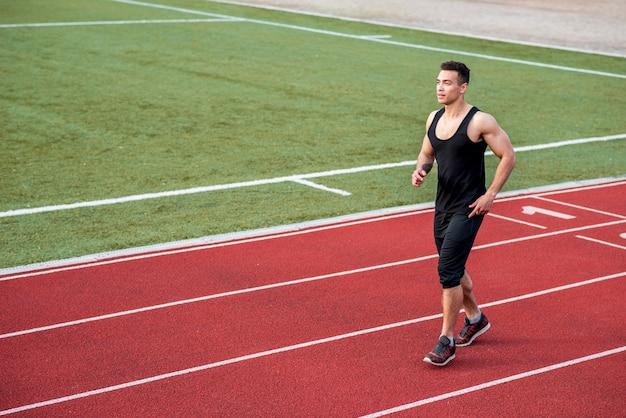 Sprawności fizycznej młoda męska atleta biega na biegowym śladzie