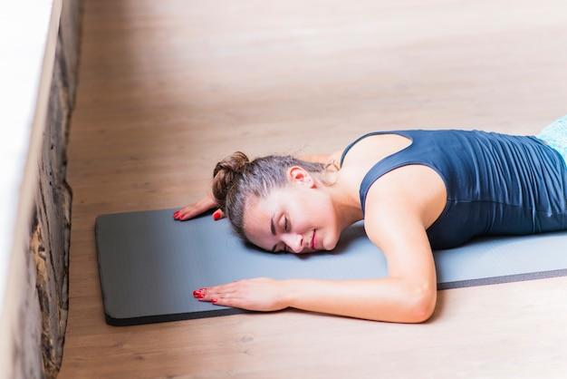 Sprawności fizycznej młodej kobiety lying on the beach na ćwiczenie macie nad drewnianym tłem