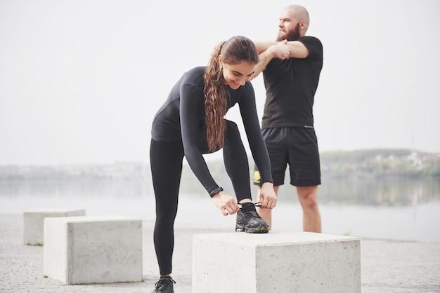Sprawności fizycznej para rozciąga outdoors w parku blisko wody. młody brodaty mężczyzna i kobieta razem ćwiczenia rano