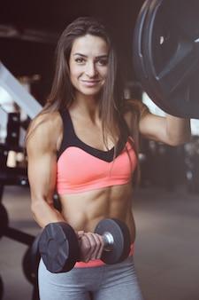 Sprawności fizycznej seksowna sportowa młoda dziewczyna pracująca w gym out