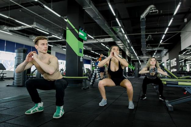 Sprawności fizycznej, sporta, treningu, gym i stylu życia pojęcie, - grupa uśmiechnięci ludzie ćwiczy w gym, robi kucnięciom