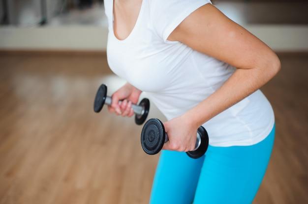 Sprawności fizycznej żeńska kobieta z mięśniowym ciałem, robi jej treningowi z dumbbells