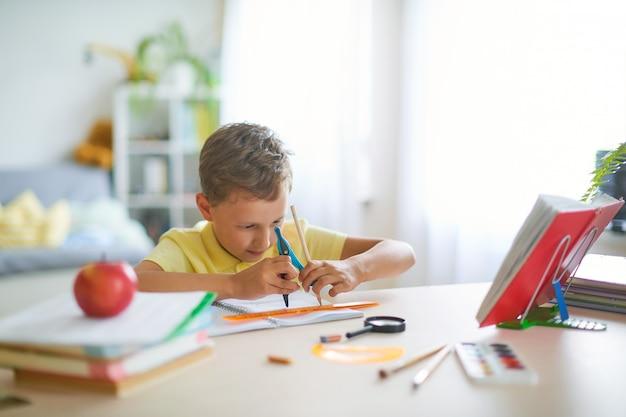 Sprawny chłopak, entuzjastycznie rysujący geometryczny kształt kompasem, koło.