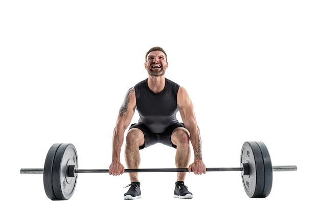 Sprawny człowiek robi ćwiczenia martwego ciągu. pełna długość na białym tle.
