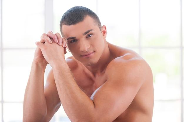 Sprawny i pewny siebie. przystojny młody muskularny mężczyzna siedzi na krześle i uśmiecha się