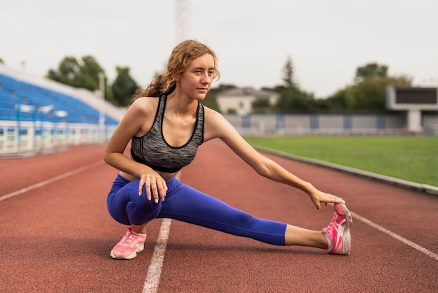 Sprawny kobieta rozciąganie przed treningiem