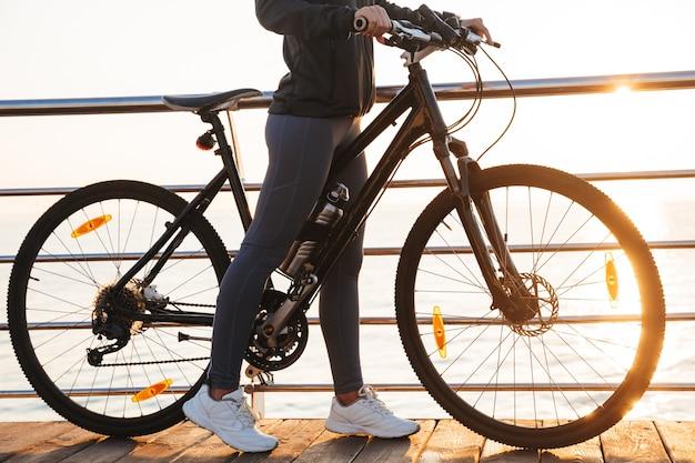 Sprawny kobieta stojąca z rowerem na promenadzie, podczas wschodu słońca nad morzem