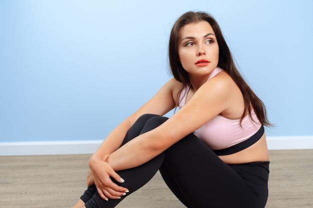 Sprawny kobieta w odzieży sportowej, siedząc na podłodze w siłowni