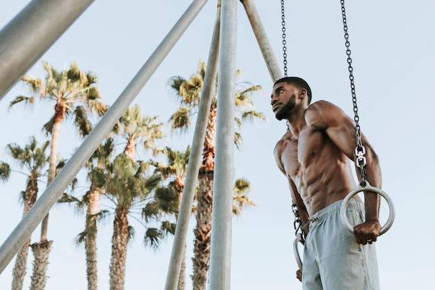 Sprawny mężczyzna ćwiczący na plaży?