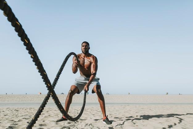 Sprawny mężczyzna ćwiczący z linami bojowymi