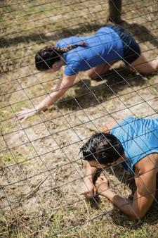 Sprawny mężczyzna i kobieta czołgają się pod siatką podczas toru przeszkód w obozie treningowym