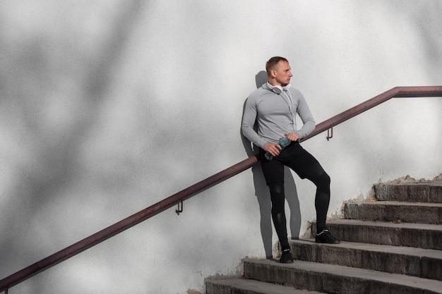 Sprawny mężczyzna siedzi na schodach i odwracając wzrok