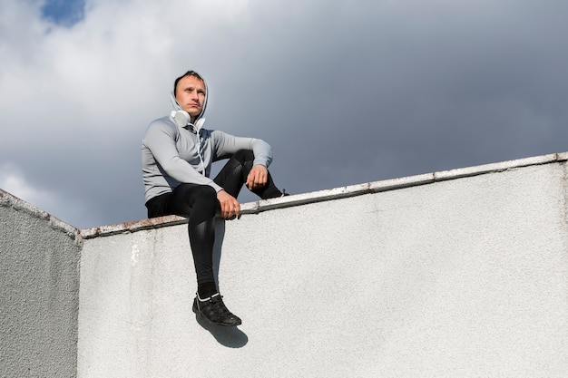 Sprawny mężczyzna siedzi na ścianie i odwracając wzrok