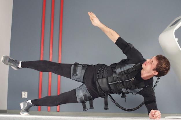Sprawny mężczyzna w elektrycznych kombinezonach do stymulacji mięśni, wykonując ćwiczenia z desek bocznych. ems.