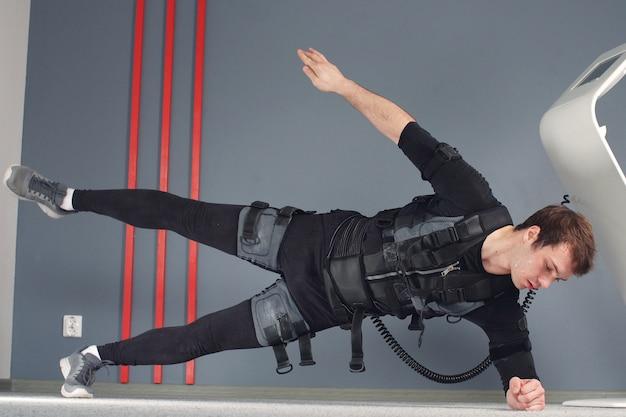 Sprawny mężczyzna w elektrycznych kombinezonach stymulacji mięśni, wykonując ćwiczenia z desek bocznych.