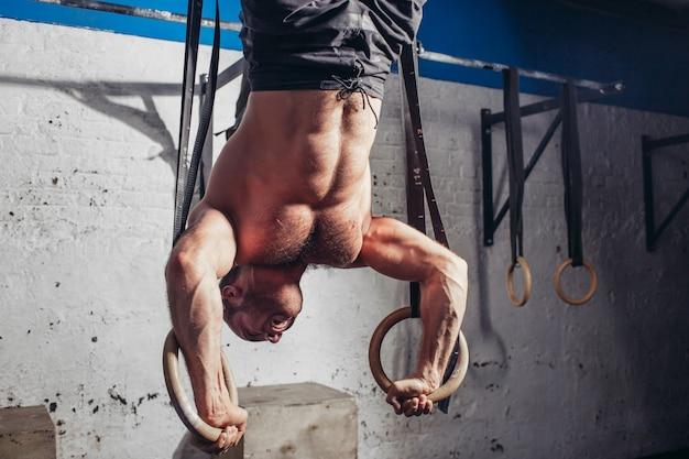 Sprawny mężczyzna wyciągając na pierścienie gimnastyczne.