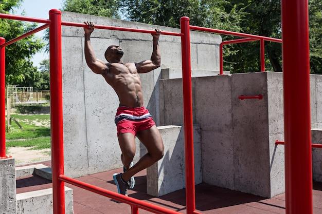 Sprawny sportowiec ćwiczeń na stadionie. afro lub afroamerykanin mężczyzna na zewnątrz w mieście