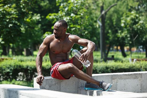 Sprawny sportowiec odpoczywa i pije wodę po ćwiczeniach na stadionie