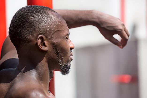 Sprawny sportowiec wykonujący ćwiczenia na stadionie. afro lub afroamerykanin mężczyzna na zewnątrz w mieście. podciągnij ćwiczenia sportowe. fitness, zdrowie, koncepcja stylu życia