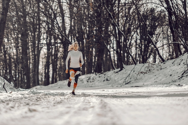 Sprawny sportsmenka na zaśnieżonej ścieżce w przyrodzie w zimie. sport, ćwiczenia cardio, fitness zimą