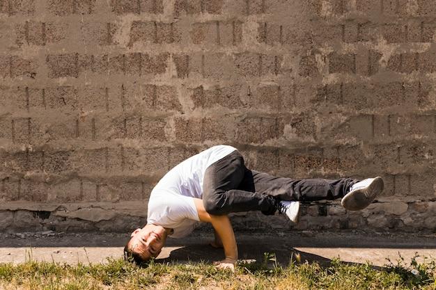 Sprawny tancerz wykonuje przeciw kamiennej ścianie