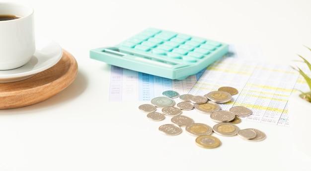 Sprawozdanie finansowe z tabelami liczbowymi, kalkulatorem i filiżanką kawy na białym biurku, koncepcja biznesowa dla finansów, gospodarki, emerytury i podatków, widok z góry z góry, kopia przestrzeń