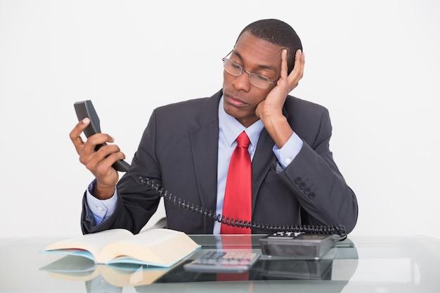Sprężający młody afro biznesmen patrzeje telefonicznego odbiorcę