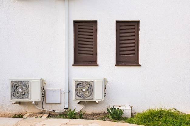 Sprężarka klimatyzacji zainstalowana na budynku.