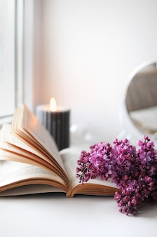 Spring flatlay w domu z bzem, książką i świeczką. sezon kwitnienia przytulny czas.