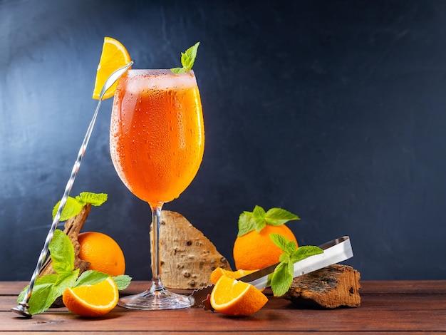 Spritz z aperolem koktajlowym i narzędzia barowe. włoski aperol spritz koktajl i plasterki pomarańczy na ciemnym tle. koktajl aperol spritz ze świeżą miętą