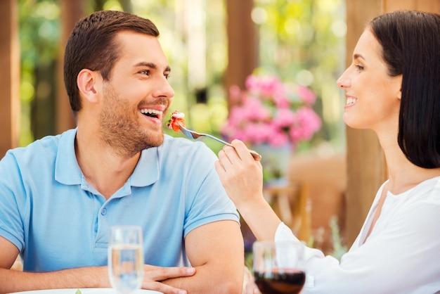 Spróbuj mojego posiłku! piękna młoda kobieta karmi swojego chłopaka sałatką i uśmiecha się, jednocześnie relaksując się w restauracji na świeżym powietrzu