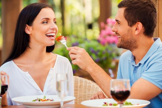 Spróbuj mojego posiłku! przystojny młody mężczyzna karmi swoją dziewczynę sałatką i uśmiecha się, jednocześnie relaksując się w restauracji na świeżym powietrzu
