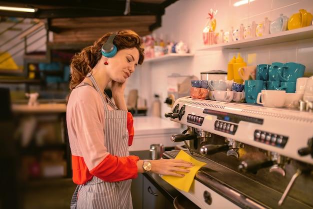 Spróbuj sie zrelaksować. miła dziewczyna słuchająca muzyki podczas pracy w kawiarni