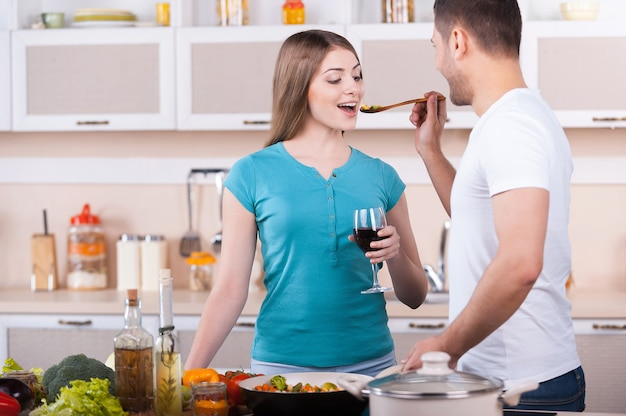 Spróbuj tego! szczęśliwa młoda para gotuje razem w kuchni