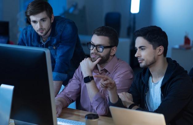 Spróbuj to sprawdzić. inteligentny przystojny brunet siedzi z kolegami przed komputerem i wskazuje na niego podczas wspólnej pracy
