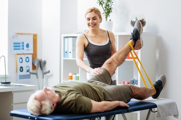 Spróbuj wyżej. miła, szczęśliwa kobieta trzymająca nogę pacjenta, pomagając mu ją podnieść
