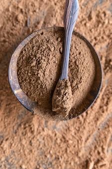 Sproszkowany chleb świętojański w drewnianej misce zamiennik kakao koncepcja zdrowej żywności