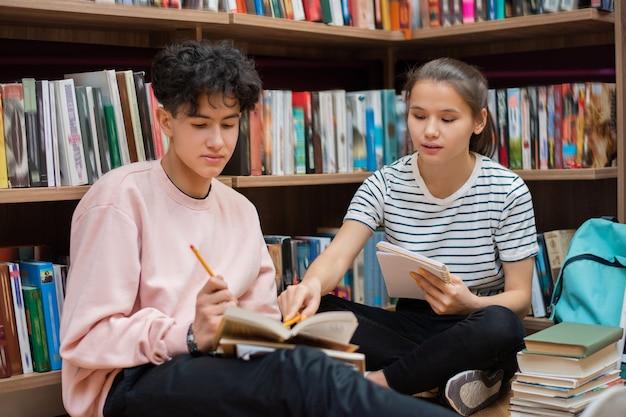 Sprytna, pewna siebie dziewczyna wskazująca na stronę z książką trzymaną przez koleżankę podczas przygotowań do seminarium w bibliotece uczelni