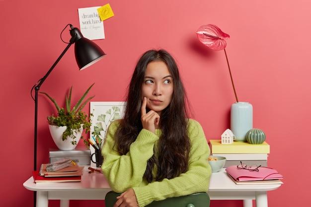 Sprytna, przemyślana studentka odwraca wzrok, zastanawia się nad czymś, myśli o zrobieniu szkicu do zegarka, przygotowuje projekt