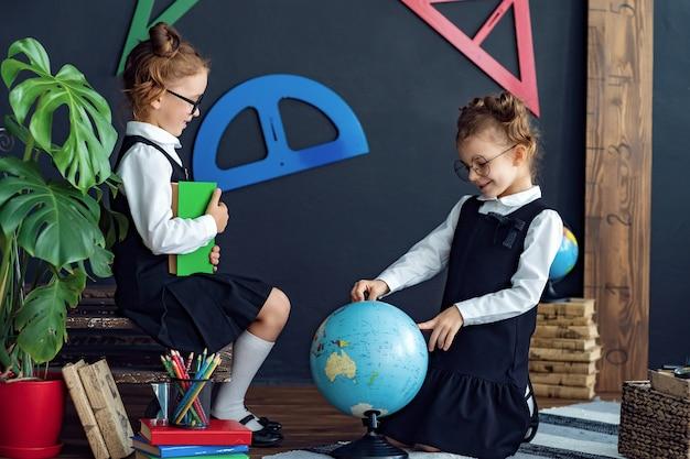 Sprytne dziewczyny czytające książki i badające kulę ziemską w szkole