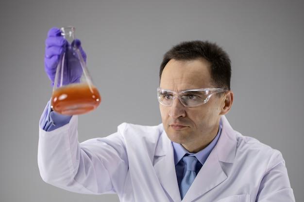 Sprytny biolog prowadzący badania w laboratorium chemicznym na szarej ścianie