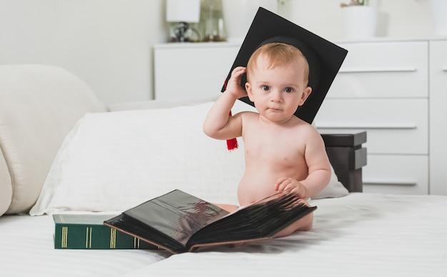 Sprytny chłopczyk w czapce dyplomowej pozuje z książkami