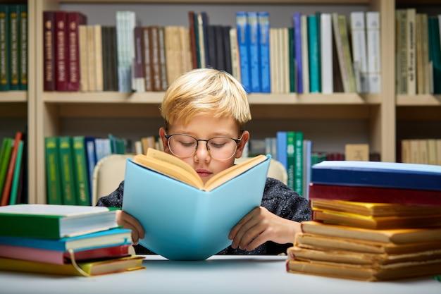 Sprytny chłopiec czytający książkę w bibliotece, lubiący edukację, przygotowujący się do szkoły, noszący okulary