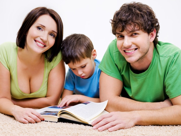 Sprytny chłopiec w wieku przedszkolnym czytanie książki ze swoimi młodymi szczęśliwymi uśmiechniętymi rodzicami