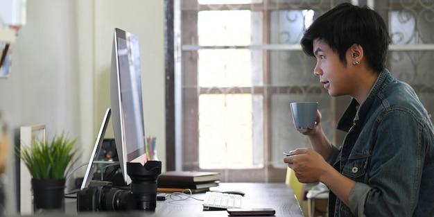 Sprytny człowiek pije kawę podczas pracy przy biurku w otoczeniu sprzętu fotograficznego.