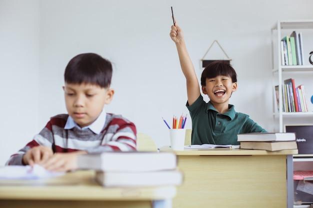 Sprytny i aktywny uczeń podnoszący rękę z podekscytowanym wyrazem twarzy podczas lekcji, aby odpowiedzieć na