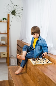 Sprytny mały szachista z brązowymi włosami i dżinsowymi ubraniami gra w szachy w pokoju